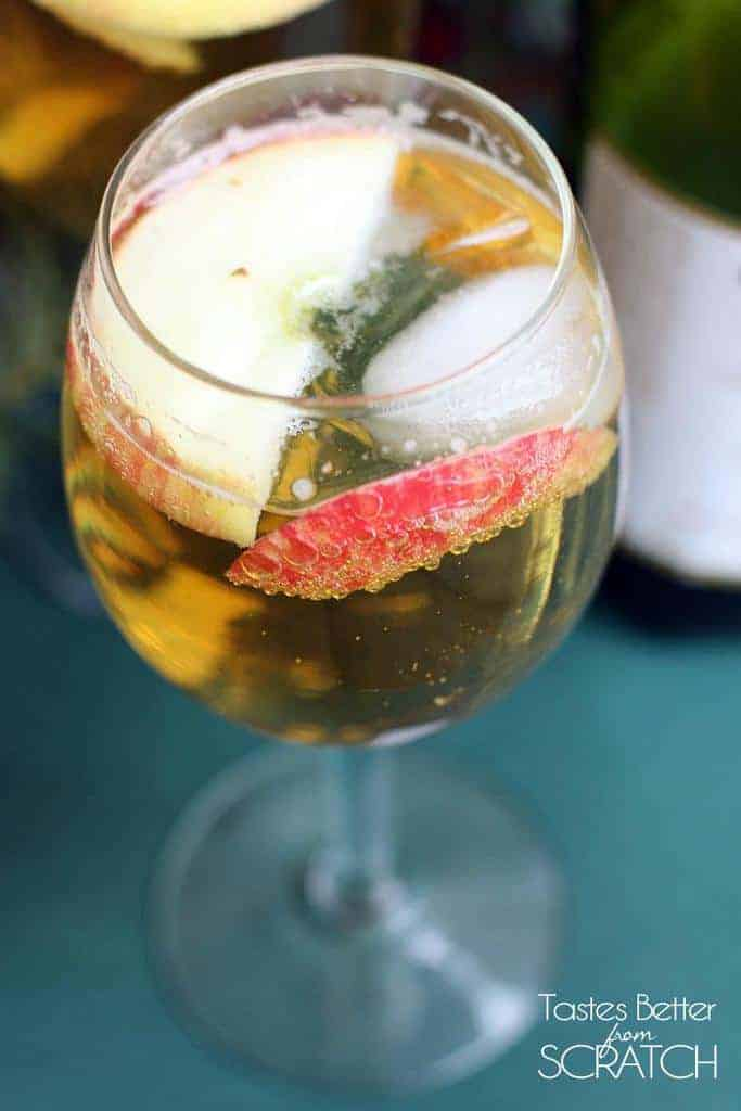 A clear glass filled with Homemade Sparkling Apple Cider (Martinelli's) with two apple slices.