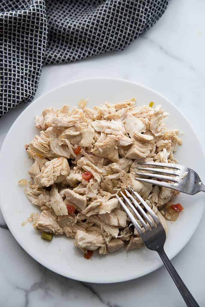 A plate full of shredded chicken with two fork resting on it.