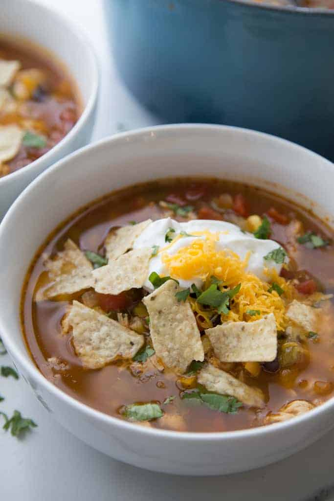 A white bowl with chicken tortilla soup in it topped with tortilla chips, sour cream, shredded cheese and cilantro.