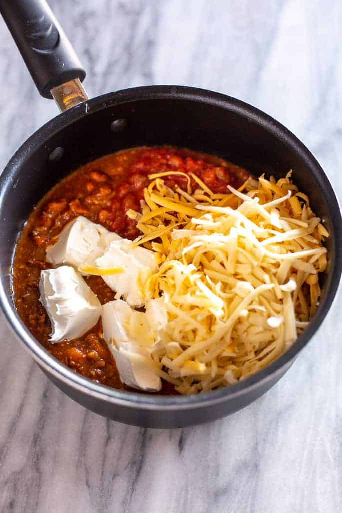 A saucepan with chili, salsa , shredded cheese and cut up cream cheese.