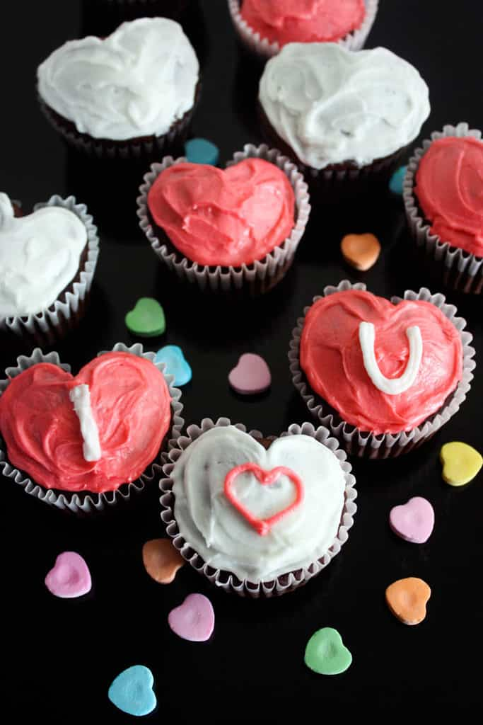 Cupcakes shaped as hearts on a black board, decorated with pink and white frosting and conversation hearts around them.
