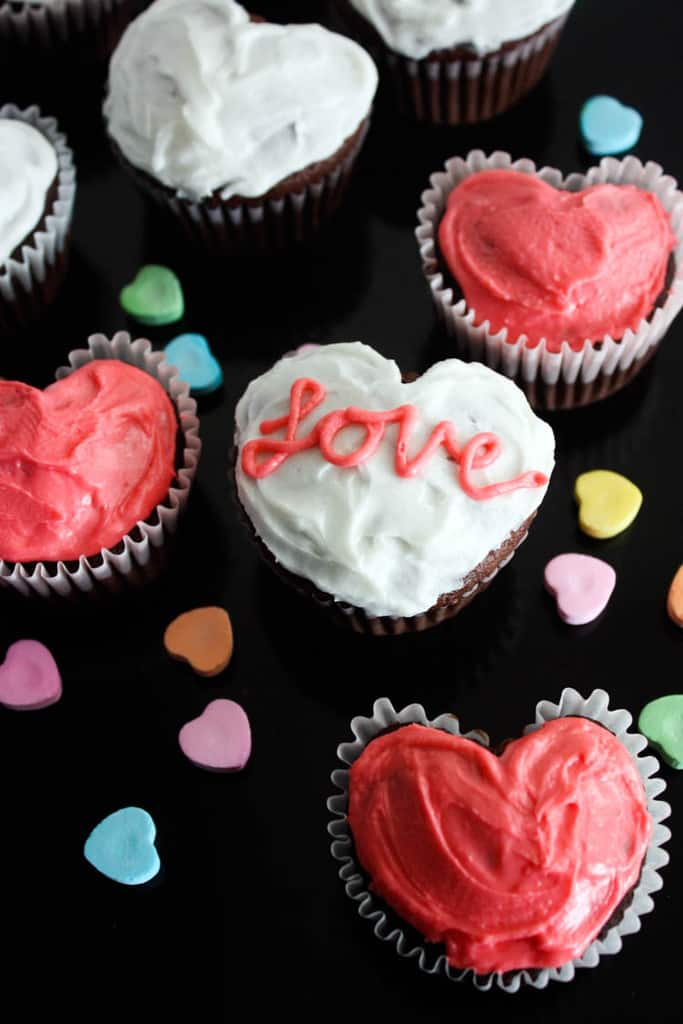 Heart Cupcakes made using a muffin tin and frosted with white and pink frosting, with heart candies in the background.