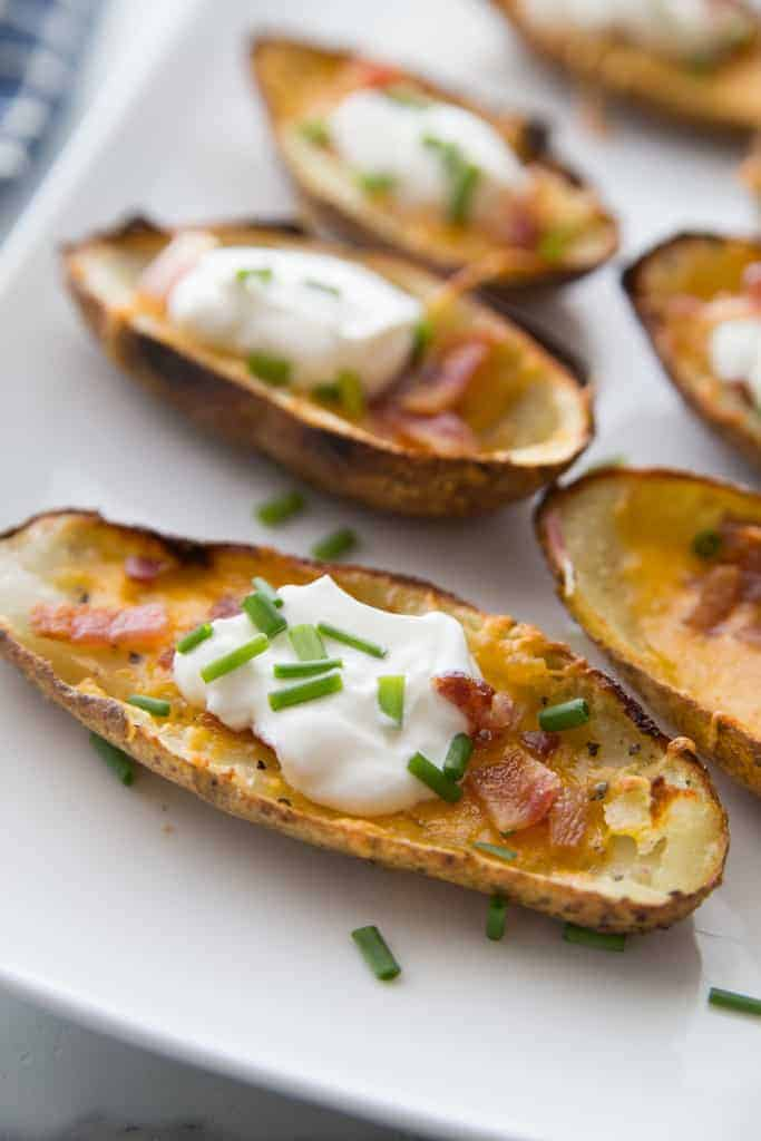 Potato skins topped with cheese, bacon, sour cream and chives, on a white platter.