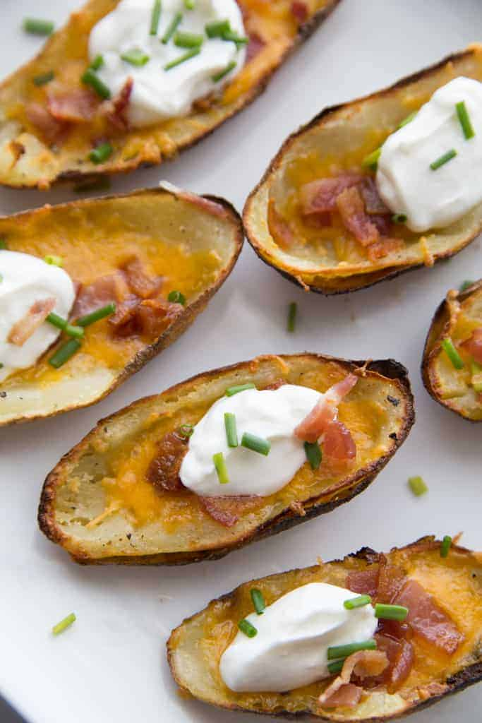 Loaded baked potato skins with cheese, topped with a scoop of sour cream and chives.