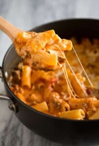Baked Ziti made in a skillet with ziti noodles, cheese and sausage, with a wooden spoon scooping out a serving.
