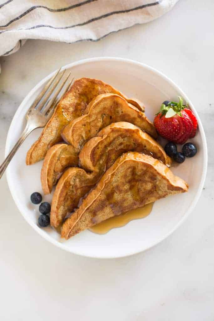 Overhead photo of a plate with four triangle slices of french toast, syrup on top and berries on the side.