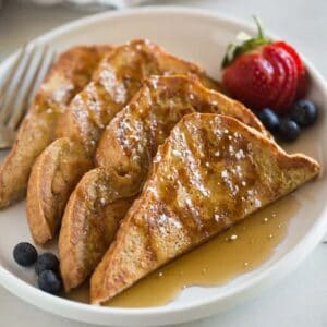A plate full of sliced french toast sprinkled with syrup and powdered sugar, berries on the side and a towel in the background.