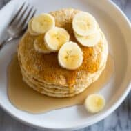 Protein Pancakes served with sliced bananas and syrup on a white plate with a fork.