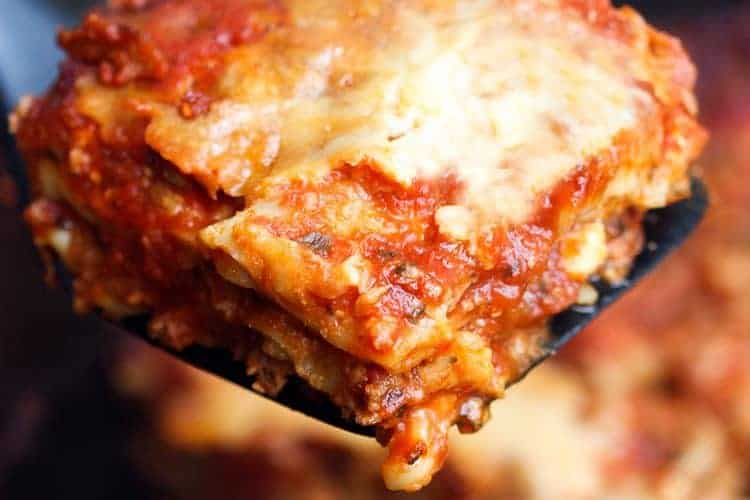 A slice of slow cooker lasagna being lifted from the crock pot.