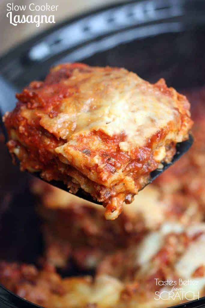 A spatula lifting one serving of slow cooker lasagna from a crock pot.