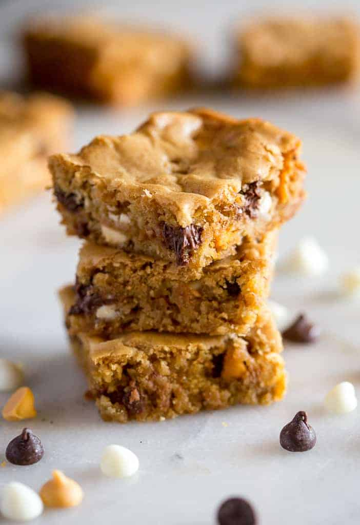 Three blondie square bars stacked on each other with chocolate chips, white chocolate and butterscotch chips scattered on the white board they're resting on.