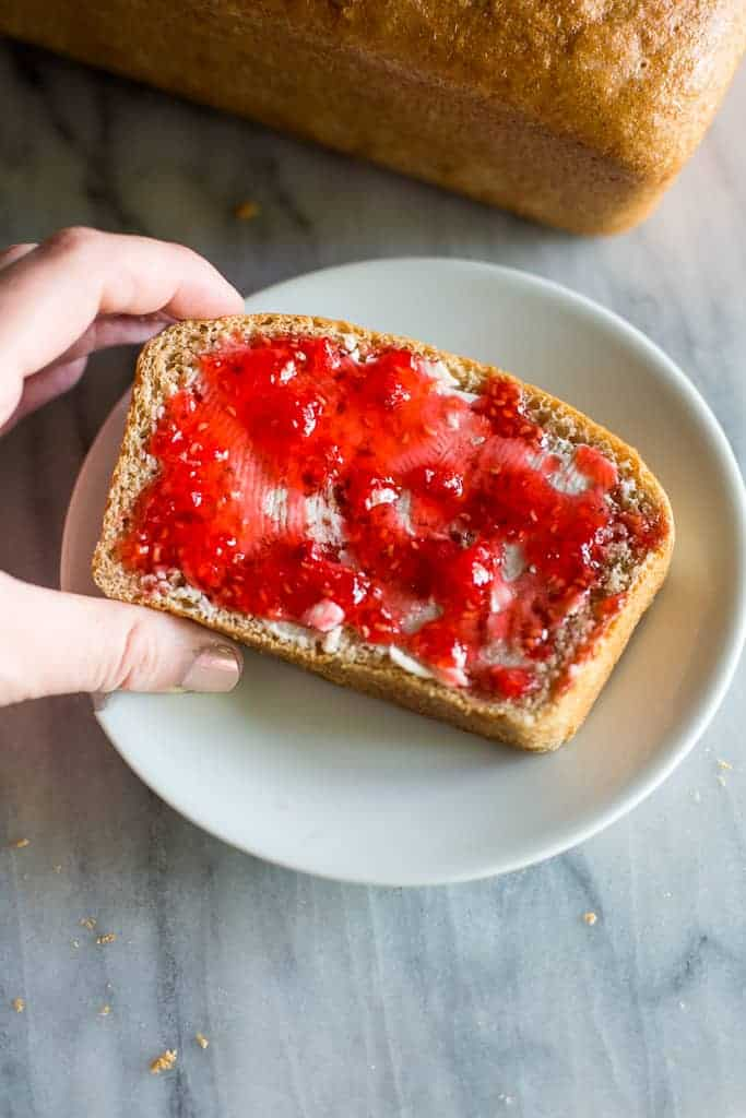 A slice of wheat bread with butter and jam on it, served on a white plate.