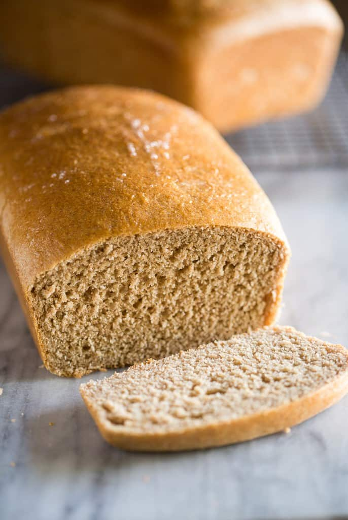 A loaf of whole wheat bead with one slice sliced off and another loaf in the background.