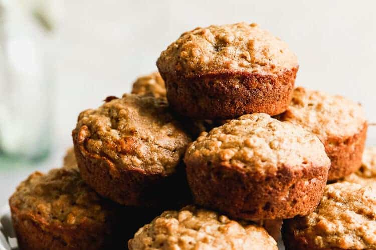 Banana Oat Muffins stacked on a plate.