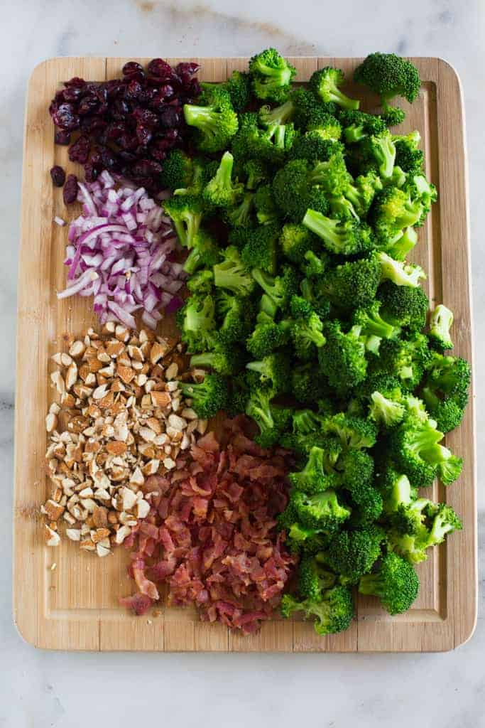 A wood cutting board with the ingredients needed for broccoli salad including broccoli florets, chopped bacon, chopped almonds, craisins and chopped purple onion.