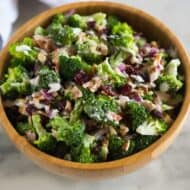Broccoli salad with bacon, craisins, almonds and a creamy dressing, served in a wooden bowl with a hand towel in the background.