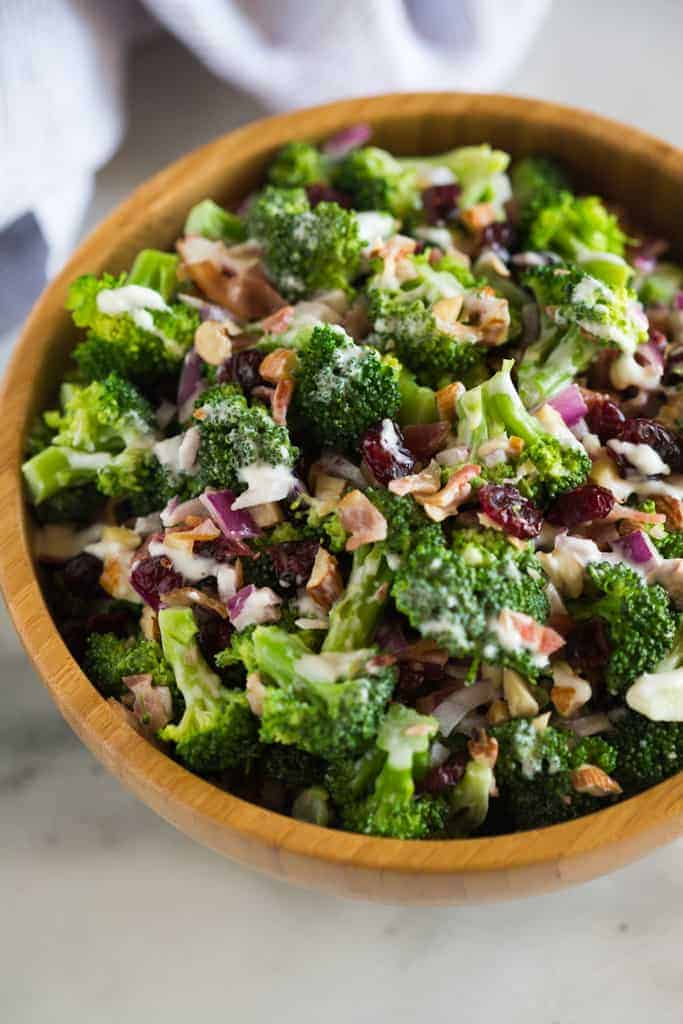 A close up photo of broccoli salad with bacon, onion, nuts and raisins served in a wooden bowl.