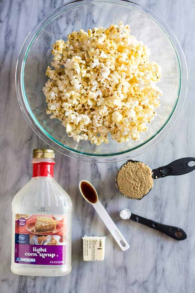 The individual ingredients needed to make caramel popcorn including a bowl of popped popcorn, corn syrup, brown sugar, vanilla, baking soda and butter.