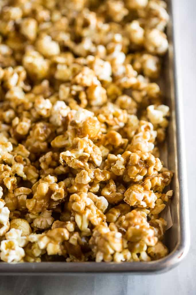 One corner of a cookie sheet with caramel popcorn in it.