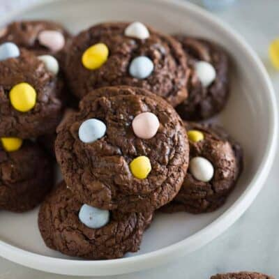 Chocolate cookies with mini cadburry egg pieces, on a white plate.