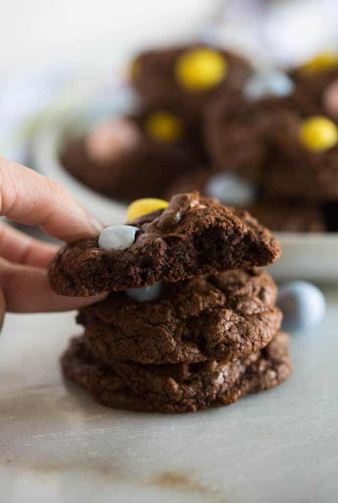 Chocolate Cadbury Egg cookies stacked on a plate with a hand grabbing the top cookie that is cut in half.