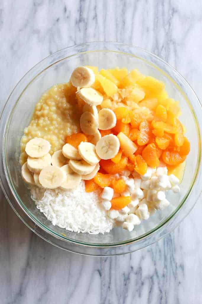 Overhead view of a bowl with the ingredients for frog eye salad including acini de pepe, crushed pineapple, bananas, mandarin oranges, marshmallows and coconut.