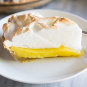 A slice of Lemon Meringue Pie served on a white plate with the remaining pie in the background.