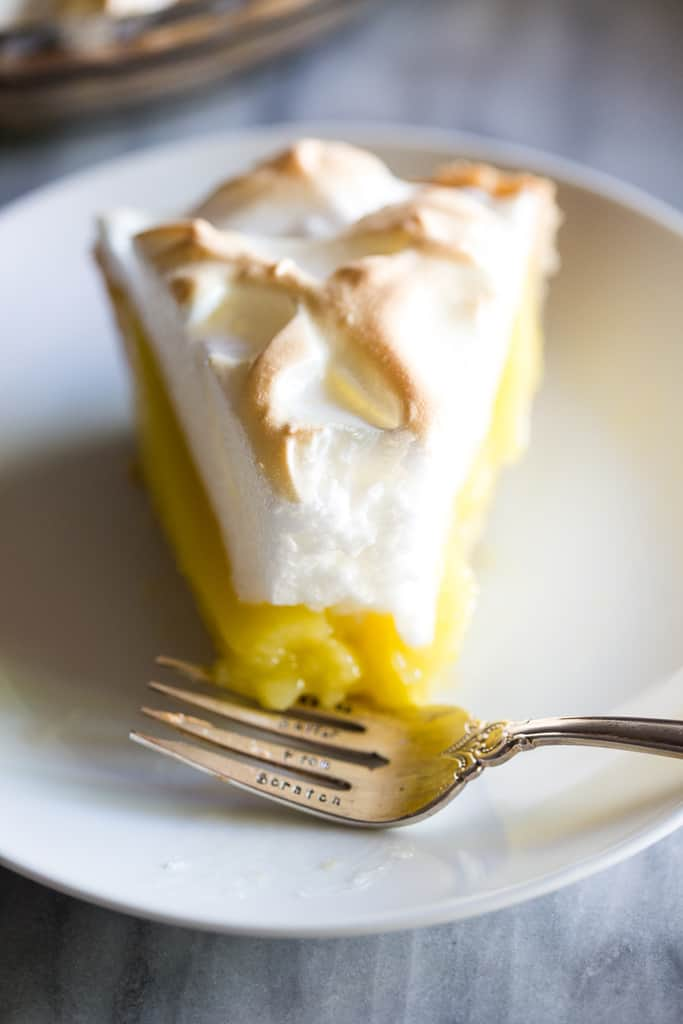 A slice of lemon meringue pie with a bite removed, and a fork on the plate.