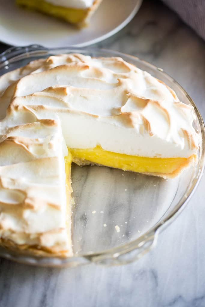 A lemon meringue pie with a large slice removed from it.