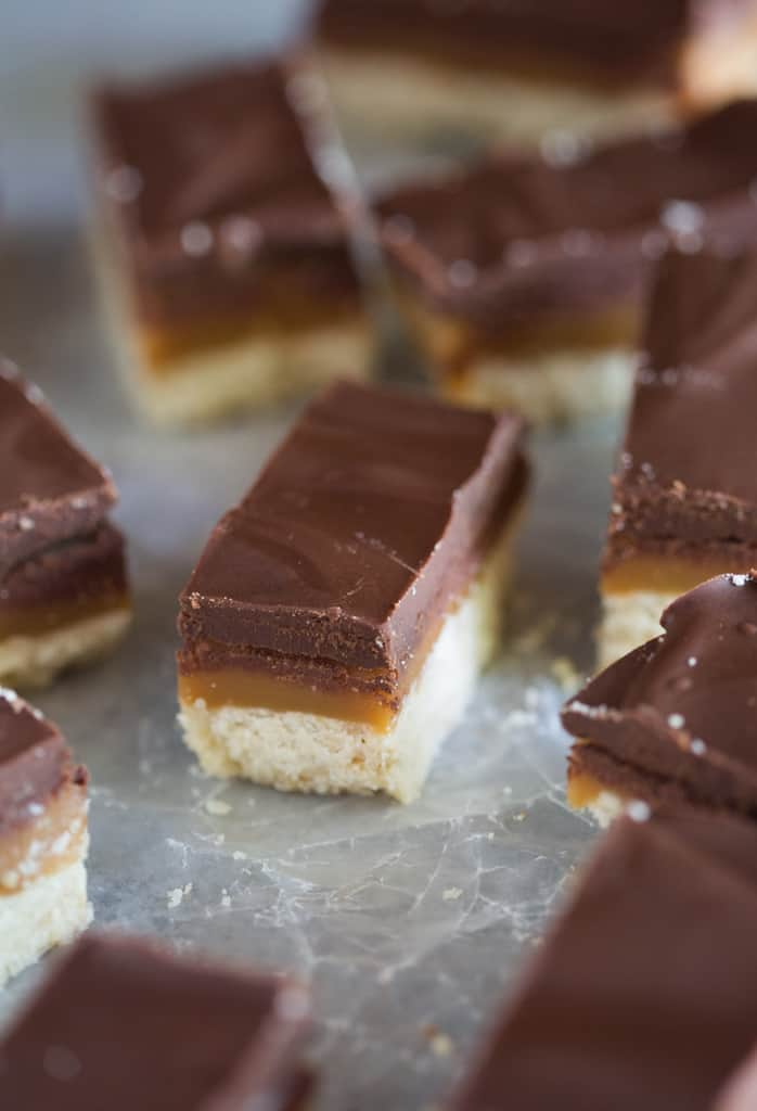 A homemade twix cookie bar with a shortbread crust, middle layer of caramel and topped with chocolate.