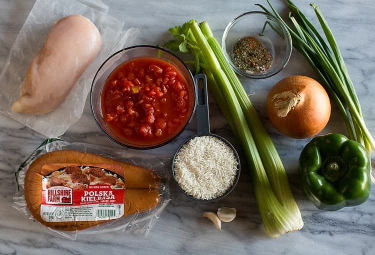 Overhead photo of the ingredients needed to make jambalaya, including raw chicken breast, sausage, white rice, diced tomatoes, celery, onion, green bell pepper, green onion, garlic cloves and a small bowl with spices in it.