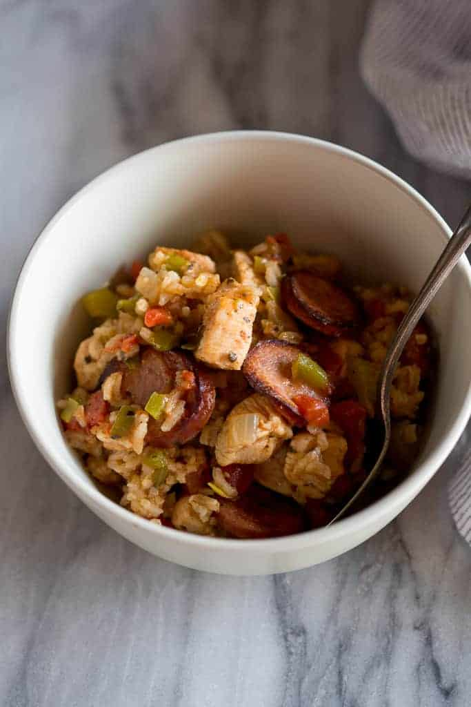 A white bowl filled with chicken and sausage jambalaya and a spoon in it.