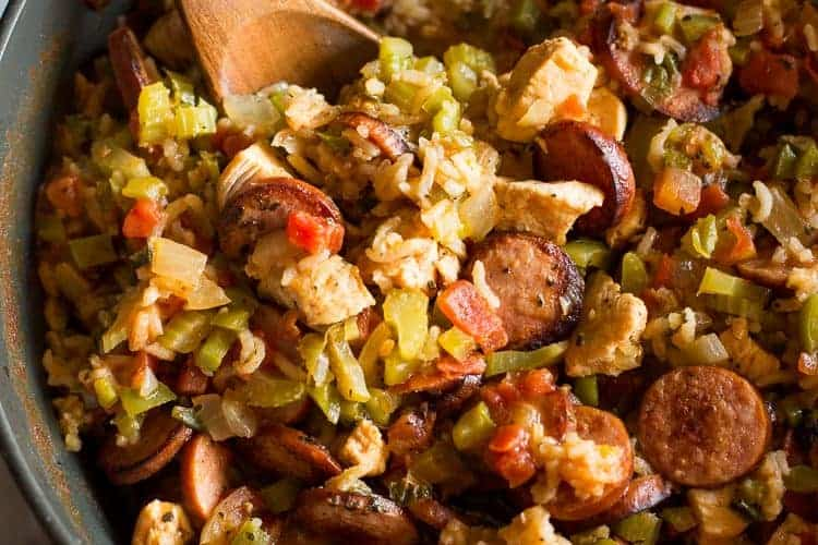 Overhead photo of a large skillet filled with Jambalaya, including rice, chicken and sausage, with a wooden spoon in the skillet for serving.