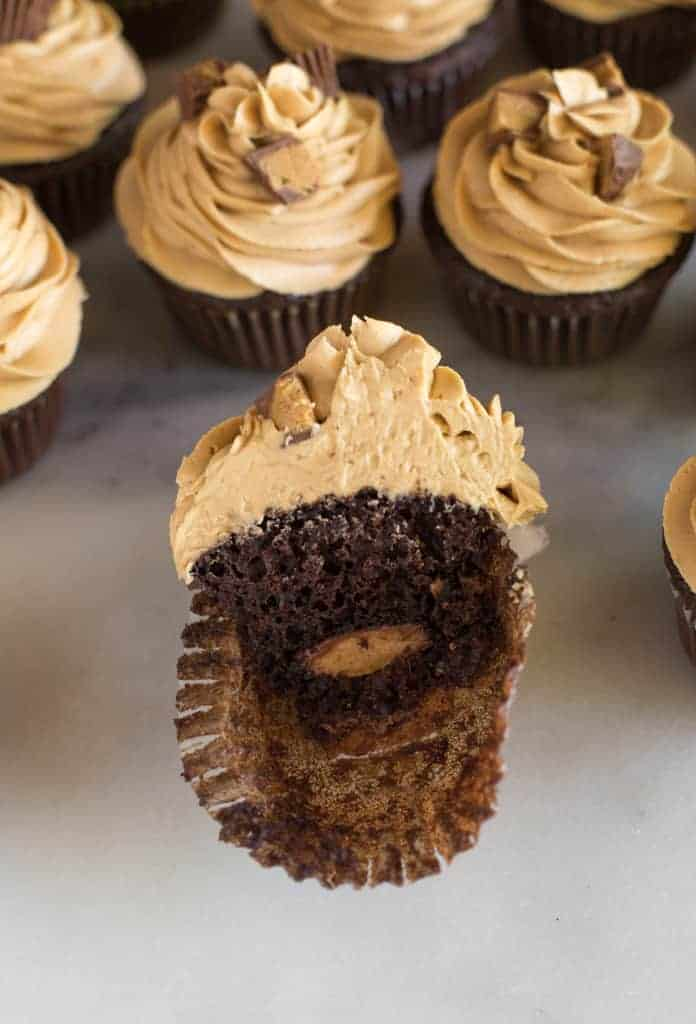 A chocolate cupcake with peanut butter frosting that has been cut in half to reveal a Reese's chocolate candy in the center of the cupcake.
