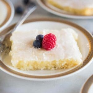 A slice of Almond Sheet Cake with a deliicous almond glaze frosting and topped with blueberries and a raspberry.