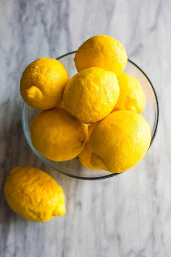 Overhead photo of a clear glass bowl with lemons in it.