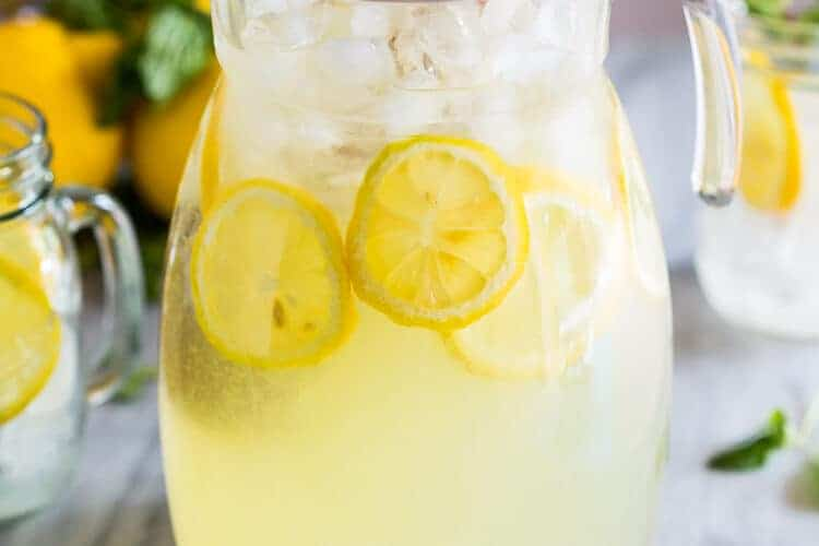 A pitcher of fresh squeezed lemonade with lemon slices and ice and lemons in the background.