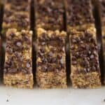 No bake granola bars with chocolate chips on top, on a white board, cut into rectangles.