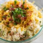 A bowl full of baked potato salad including chopped potatoes, bacon, green onions and shredded cheese.