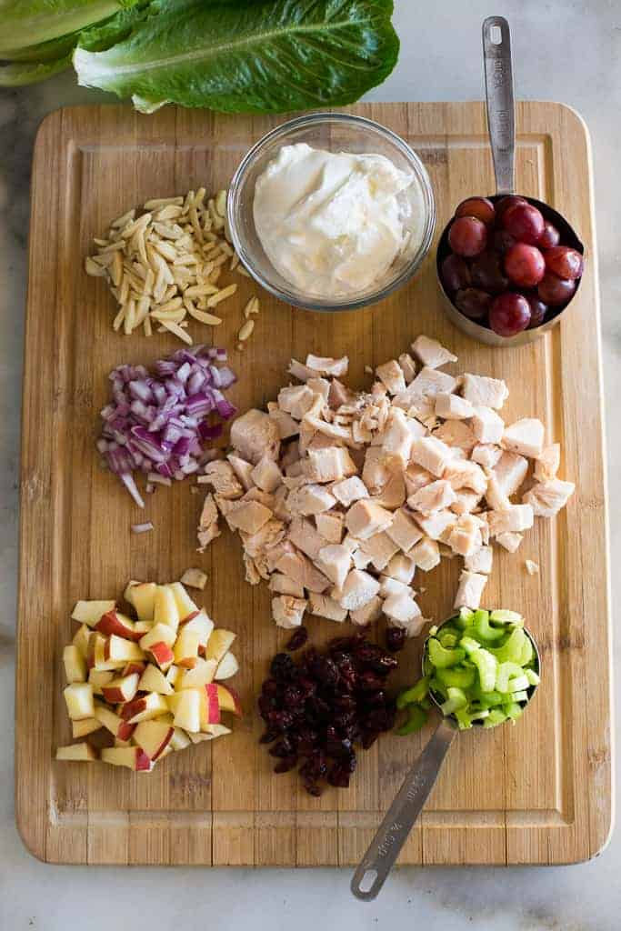 A wood cutting board with the ingredients for chicken salad including chopped chicken, onion, celery, craisins, apples, grapes and Greek yogurt.
