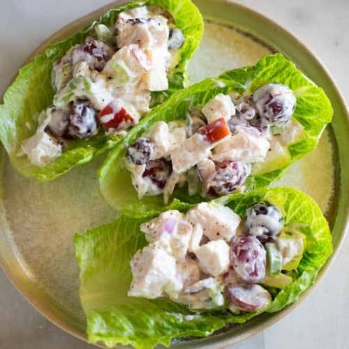 Three lettuce cups on a plate filled with chicken salad mixture with cut grapes and apples in it.