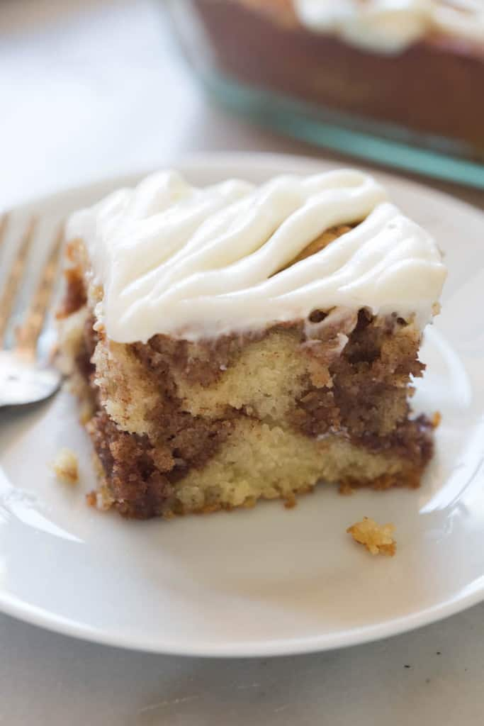 A slice of cinnamon roll cake with cream cheese frosting on a plate.
