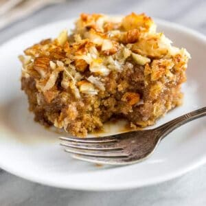 A slice of oatmeal cake on a white plate, with a fork, and I bite taken out of it.