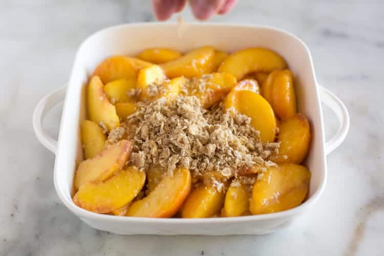 A white casserole dish filled with fresh peaches and a crumb topping being sprinkled on top of them to make peach crisp.