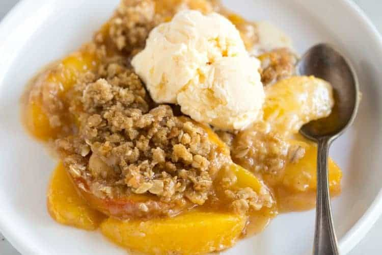 Peach crisp served with a scoop of vanilla ice cream on top, on a white plate with a spoon.