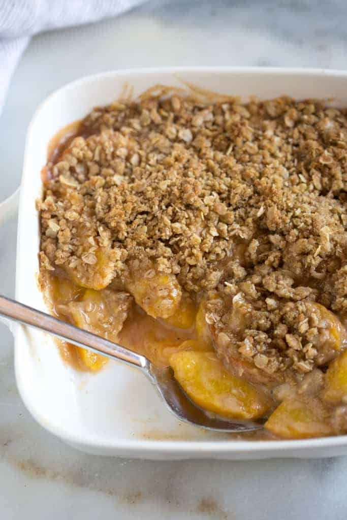 A white 8x8 inch dish filled with peach crisp with a serving removed and a spoon resting in the pan.