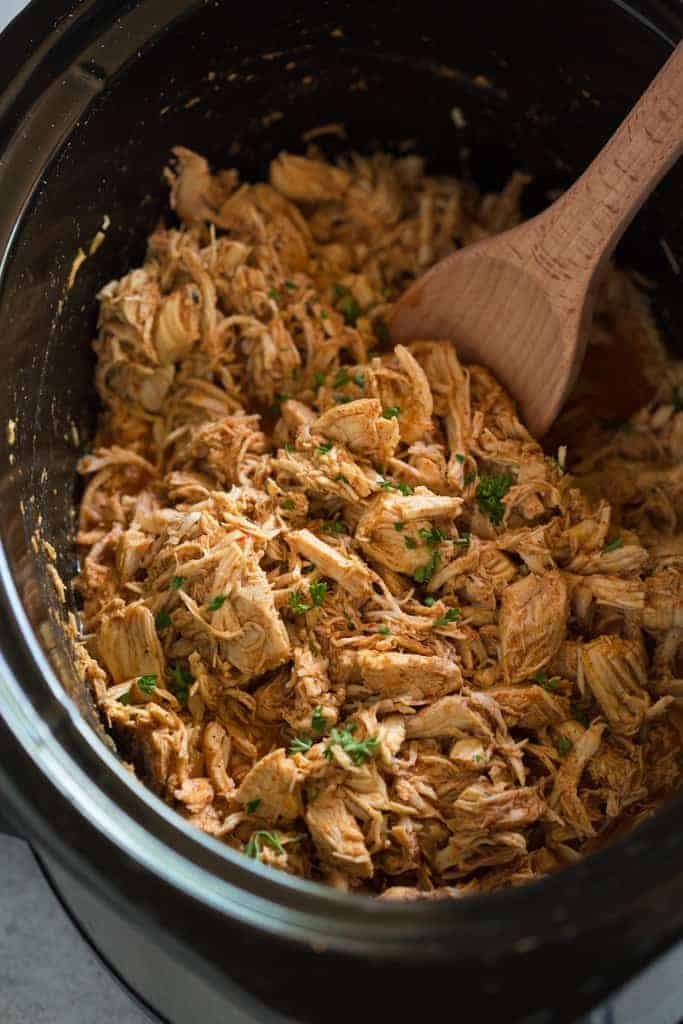 A slow cooker filled with shredded chicken to make chicken tacos.