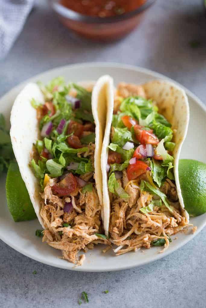 Two chicken tacos on a plate with limes and salsa in the background.
