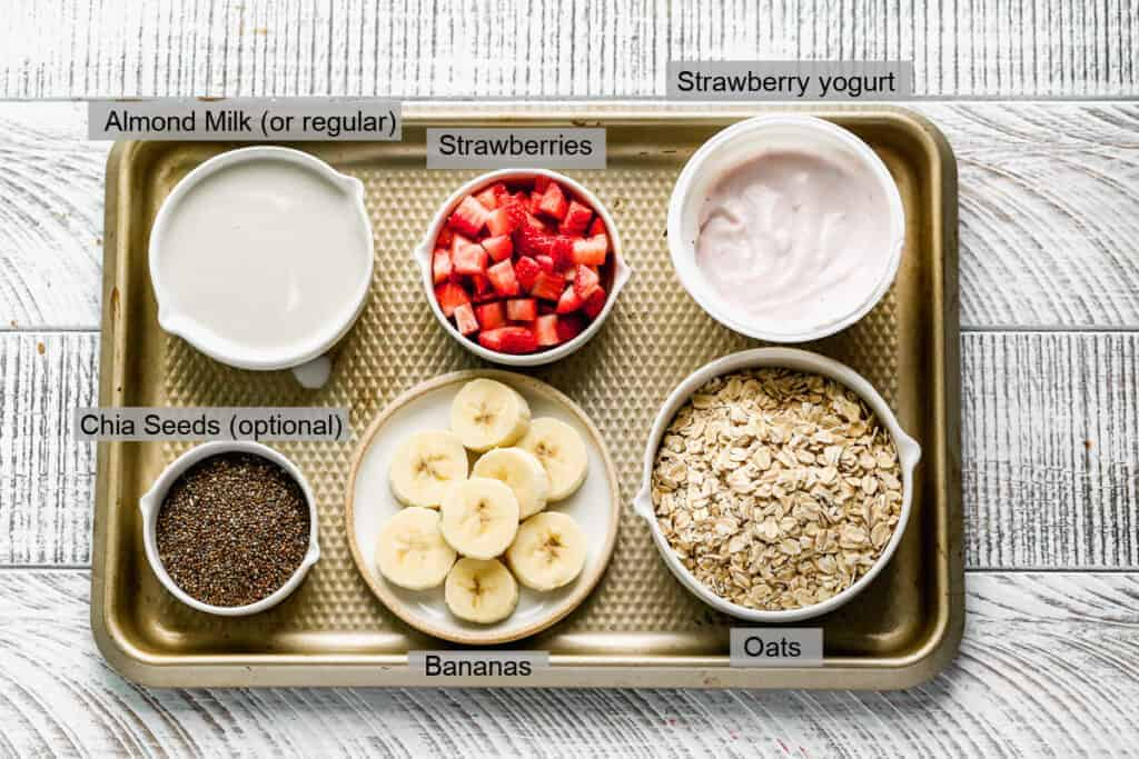 A baking tray with bowls containing the, labeled, ingredients needed to make Strawberry Overnight Oats.