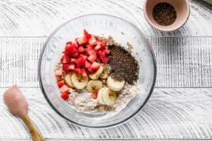 A mixture of oats, milk and yogurt in a bowl, topped with fresh strawberries, bananas and chia seeds.
